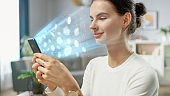 Visual Effect of Connecting and Surfing the Web with Illustrative Icons and Symbols. Handsome Young Woman Uses Smartphone in Her Living Room. Browsing in Internet, Social Networks, Relaxing at Home.