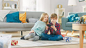 At Home: Cute Little Girl and Sweet Boy Playing Video Game on a Smartphone, Boy Holds Mobile Phone in Horizontal Landscape Mode. Children Playing in Online Videogame Sitting on a Carpet.