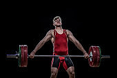 Young weightlifter lifting barbell