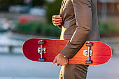 Contemporary businessman standing in the street and holding a skateboard
