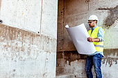 Reading blue print at construction site
