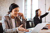Beautiful female customer service talking on the headset with client and smiling