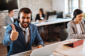 Man customer service talking on the headset with client and smiling