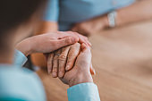 Woman holding senior woman's hand