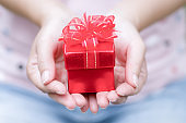 Hands holding craft paper gift box with as a present for Christmas, new year, valentine day or anniversary