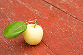 Green fresh apple on wooden table close up, rustic style, selective focus