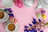 Cup of coffee with milk or latte, macaroons and milk jar on pastel pink background decorated with muscari and hyacinth flowers. Top down, flat lay. Dessert concept. Copy space.
