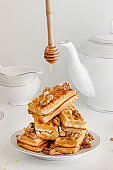 A stack of waffles with honey and walnuts on white background. Sweet delicious breakfast. Vertical