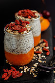 Close up of chia seed pudding with goji berries, smashed fresh apricot and oat meals on black background, vertical. Healthy balanced food concept