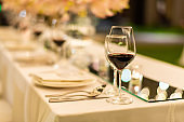 Beautiful wedding table setting decor with glasses of red wine.