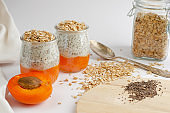 Chia seed puddings with fresh apricot and oat meals on white with a space for text. Clean eating, dieting food concept
