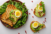 Healthy eating. Avocado toasts with egg, arugula salad and pomegranate seeds on white background. Top view, flat lay