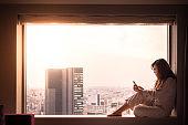Woman in pajamas using smartphone in hotel in Shibuya, Tokyo, Japan