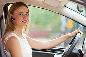 woman driving car with headset