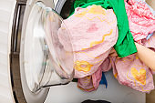 Person putting clothes into washing machine