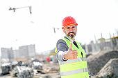 Handsome senior engineer wearing hardhat at construction site