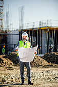 Cheerful positive handsome senior engineer  wearing hardhat satisfied with building plan holding blueprint while working at construction site
