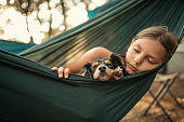 Girl relaxing in hammock with her dog