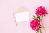 Mockup white greeting card and envelope with red peonies on a pink background