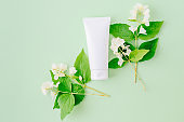 Flat lay composition with cosmetic products, mockup white tube and  jasmine flowers with green leaves on a green backgrounds