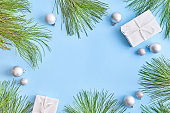 Flat lay christmas frame with pine branchesh and gift box on a blue background
