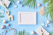 Mockup white frame with pine branches and gift box on a blue background