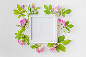 Mockup square white frame with pink flowers on a white background