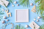 Mockup square white frame with pine branches and gift box on a blue background