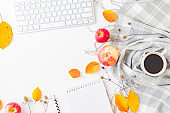 Flat lay blogger or freelancer workspace with a notebook, keyboard, scarf and colorful autumn leaves on a white background