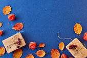Flat lay frame with colorful autumn leaves and gift box on a blue background