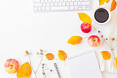 Flat lay blogger or freelancer workspace with a notebook, keyboard, sweater and colorful autumn leaves on a white background