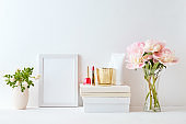 Home interior with decor elements. White frame, pink peonies in a vase, cosmetic set