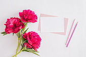 Mockup white greeting card and envelope with red peonies on a white background