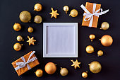 Mockup square white frame with gold christmas balls and gift box on a dark background