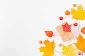Flat lay frame with colorful autumn leaves and gift box on a white background
