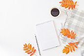 Flat lay blogger or freelancer workspace with a notebook, scarf and colorful autumn leaves on a white background