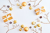 Flat lay frame with gold christmas balls, branches and gift box on a white background