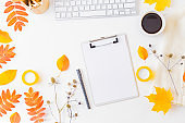Flat lay blogger or freelancer workspace with a clipboard, keyboard, sweater and colorful autumn leaves on a white background