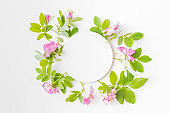 Mockup round white frame with pink flowers on white background