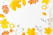 Flat lay composition with a sweater and colorful autumn leaves on a white background