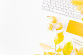 Flat lay blogger or freelancer workspace with a notebook, keyboard, colorful autumn leaves on a white background