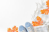 Flat lay composition with a sneakers, scarf and colorful autumn leaves on a white background