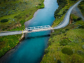 Car driving over bridge in Iceland. Stock photo.