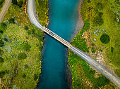 Car driving over bridge in Iceland with fresh water running under. Stock photo.