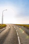 Asphalt road against sky on sunny day