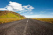 Empty road by mountains against sky in Iceland