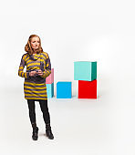 Studio shot of a woman in front of colored boxes.