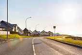 Empty road along houses on sunny day in Iceland
