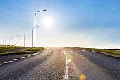 Bright sun shining over asphalt road.