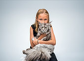 Portrait of girl carrying cute Maine Coon cat